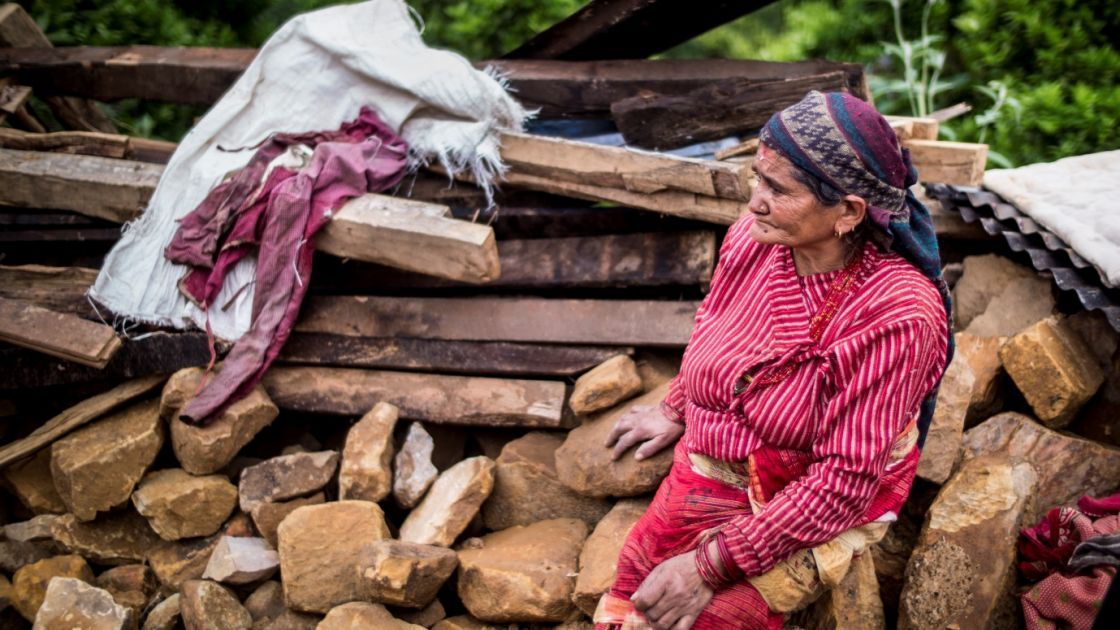 In the Nepalese village, Kukhreta, a woman sits on the rubble of her recently-destroyed home. Photo taken by Crystal Wells/Concern Worldwide
