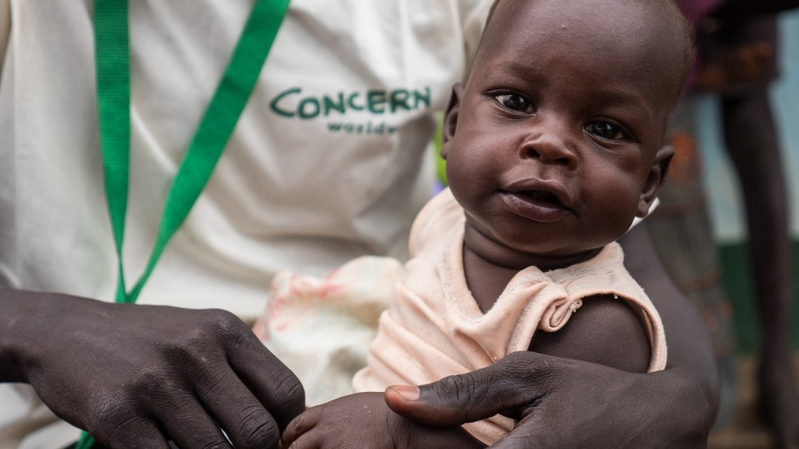 Chan Akeen Akeek's pictured smiling after a course of therapeutic food provided by Concern in Gokmachar Primary Health Care Centre, Aweil, South Sudan. Photographer: Kevin Carroll/Concern Worldwide 2016