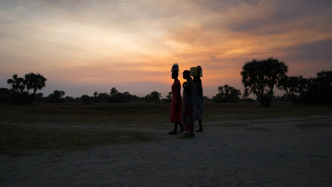 Women crossing in Leer County, Unity State, South Sudan at sunset. Deep in the swamps, the island has become a haven for thousands of people fleeing conflict. Photo: Kieran McConville/Concern Worldwide
