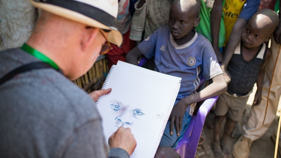 Irish artist Brian Maguire sketches a young boy in the POC of Bentiu, South Sudan. Photo: Steve De Neef / Concern Worldwide.