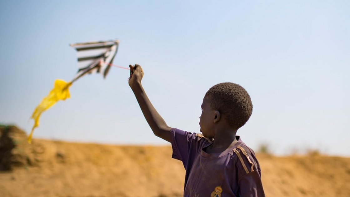 A young boy flies a home made kite on the streets of Juba's PoC in South Sudan. Photo: Steve De Neef / Concern Worldwide.