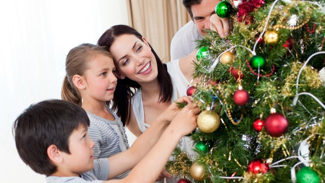 Happy family decorating a Christmas tree with boubles in the living-room