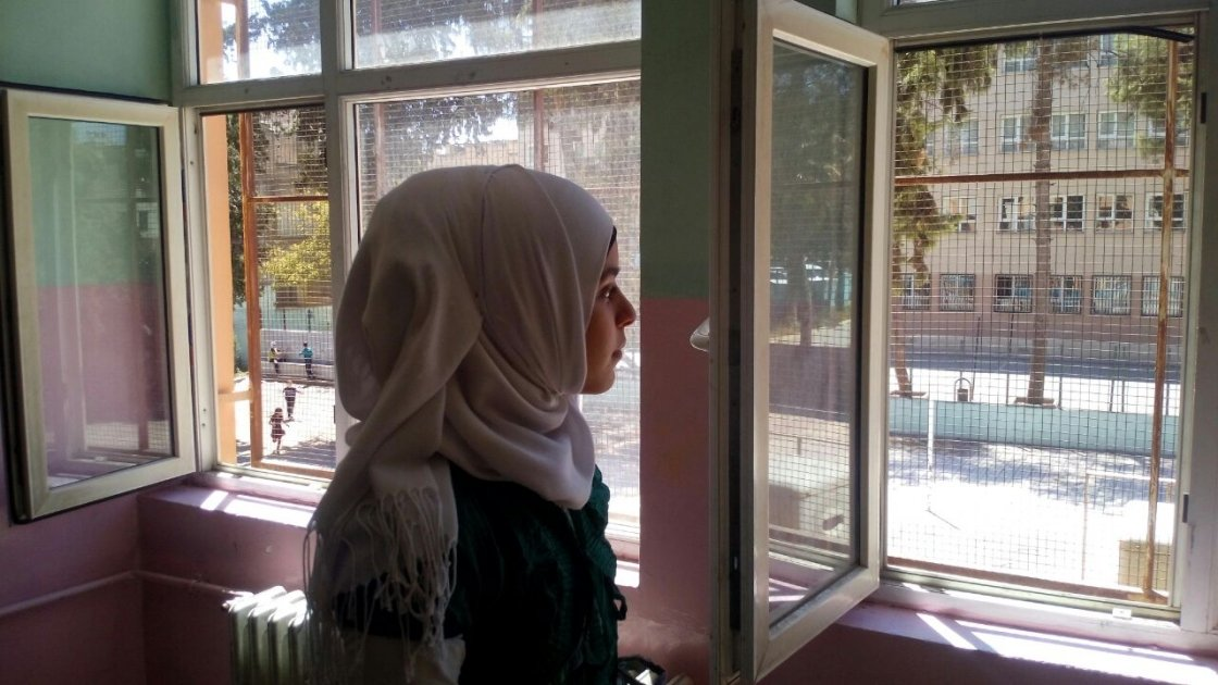 Hasna looks from her classroom window during a break from her studies in a Temporary Education Centre for Syrian refugees in Turkey. Photo: Concern Worldwide.