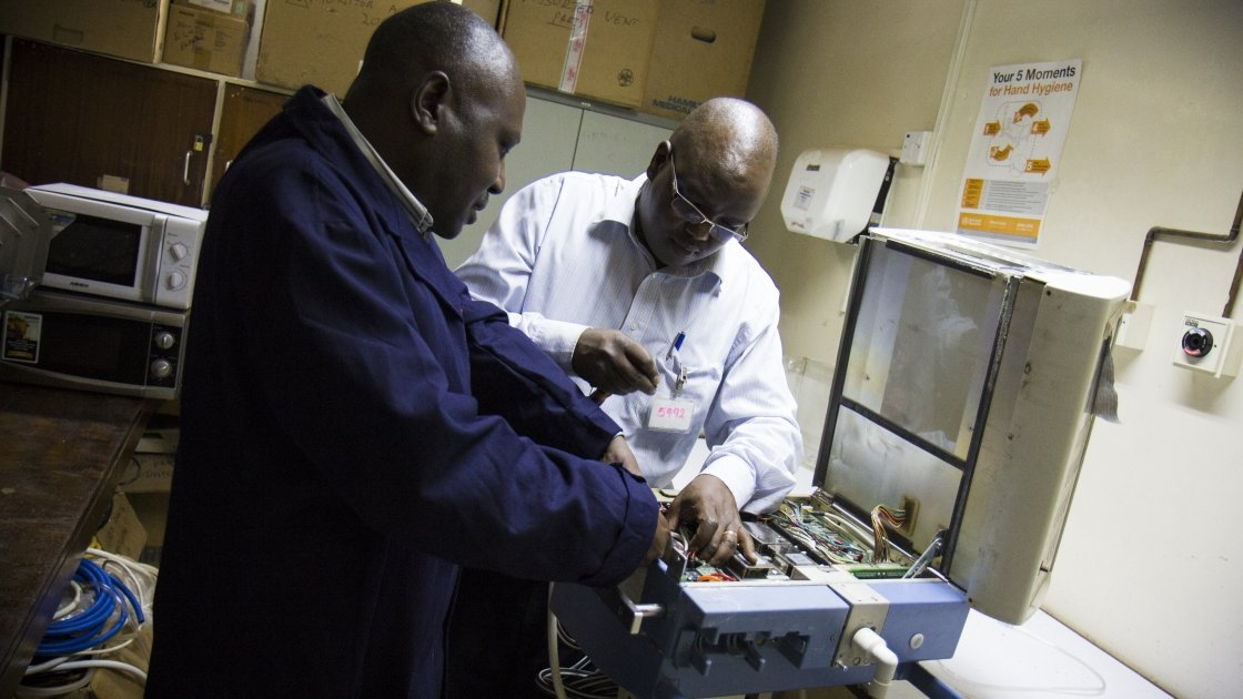 Shadrack Wamwayi and Steve Belle, biomedical engineers working on equipment at the Kenyatta National Hospital, Nairobi, Kenya, 2014. Photo: by Crystal Wells / Concern Worldwide.