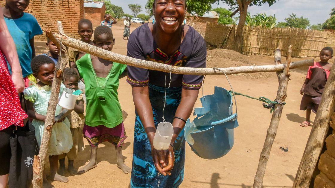 Virigita Gasiyamo, mother-of-five, Mazawe, Mchinji district washes her hands at the tippy-tap. Photo taken by Concern Worldwide.