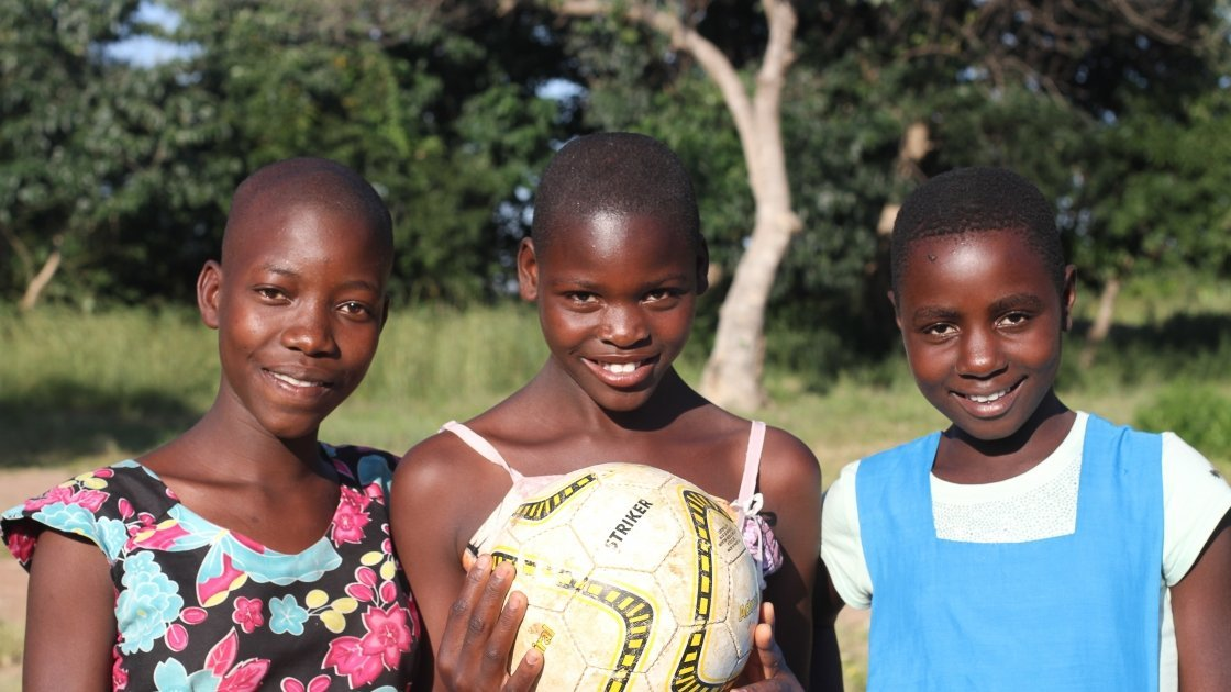 Three young woman holding a soccer ball.