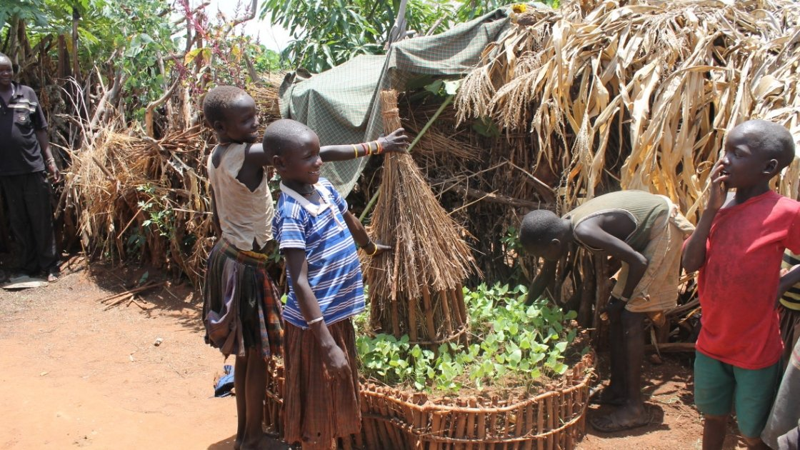 Young children proudly display the keyhole garden they established to help a mother who had just delivered twins. Napak District, Uganda. Photo: Lauren Rogers-Bell/Concern Worldwide.
