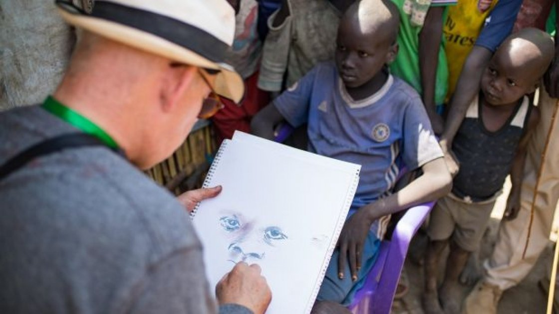 Brian Maguire sketches a young boy in the PoC camp in Bentiu, South Sudan. Photograph: Steve De Neef/Concern Worldwide