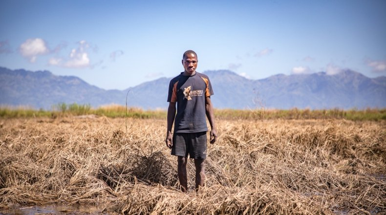 Recently married Patrick Ghembo of Monyo Village standing in his field, destroyed by the floods. Patrick is a farmer of maize and rice. He must rely solely on fishing until he can plant again. His wife and him will stay at the displacement camp until the floods have fully subsided. Photo: Gavin Douglas/ Concern Worldwide.