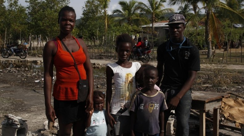 The François family, standing among the rubble of what used to be their home. They evacuated during the hurricane in 2016. Photo: Kristin Myers/Concern Worldwide
