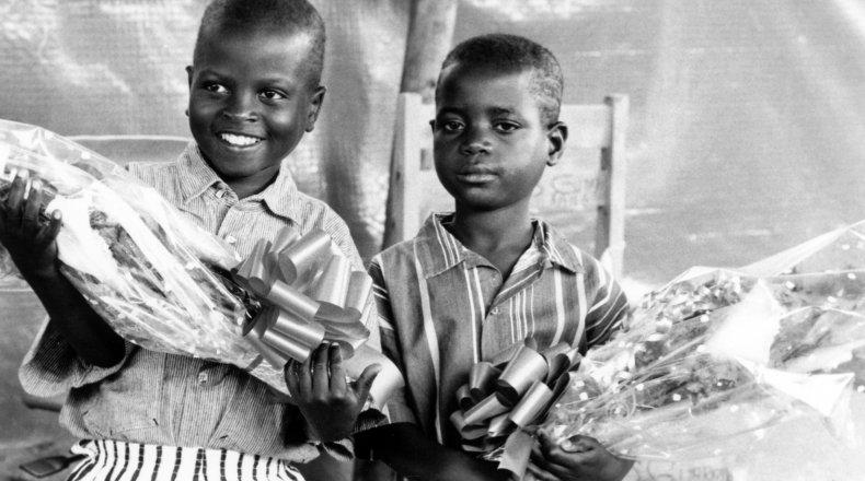 Two children hold flowers at the Runda transition camp in Rwanda. Photo: Concern Worldwide (1997)