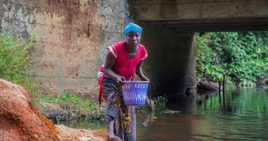 Woman collects water in bright plastic bucket.