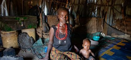 Child sits on floor of hut beside his mother, both look at the camera