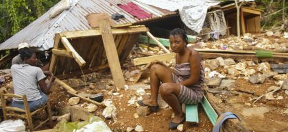 A resident of Camp-Perrin sits outside her house which was destroyed by the 7.2 magnitude earthquake in Haiti.