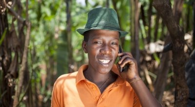 Olivier Irankunda (23) uses his mobile phone at his home in Mabayi, Cibitoke. Photo: Abbie Trayler-Smith / Concern Worldwide.