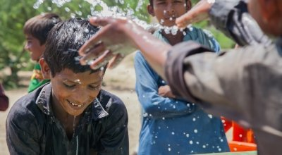 Somro and Kishore from Satla Bheel village are playing with water at the newly installed plant system.  Thar Desert, Pakistan. Phot: Black Box Sounds / Concern Worldwide.s