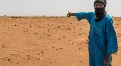 Mahamadou Islam Garmaz, Chief of Garmazaye village, points to the arid landscape