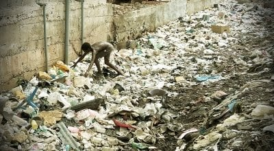 A boy searches through waste in an alleyway.
