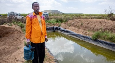 A lead farmer stands by his water catchment system in North Somaliland. As part of the climate change adaptation work, Concern provided him with a tarpaulin to which he has sank into a hole to store as much water as he can for his crops during the dry season.