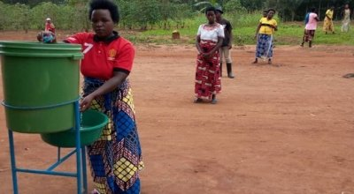 Beneficiaries washing hands in Rwanda as part of an Irish Aid-funded distribution of tools and face masks.