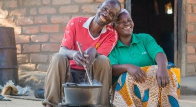 Chibala, 55, cooks at his home in May 2014 in Zambia with his wife Catherine, 43, sat next to him. Photo: Gareth Bentley / Concern Worldwide.