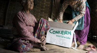 Ratna Khatri, 88 years of age, sits in the makeshift shelter her family has built since their home was destroyed in the earthquake as her granddaughter goes through the box of supplies that Concern distributed. Dolakha District. Photo: Brian Sokol.