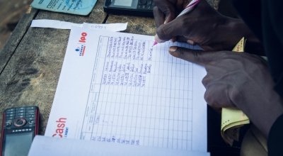 Nijimbere Alphonsine, NGO Concern staff member giving out cash transfers. Photo: Irenee Nduwayezu / Concern Worldwide.