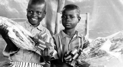 Two children hold flowers at the Runda transition camp in Rwanda. Photo: Concern Worldwide (1997)