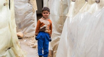 A young Syrian refugee stands between the tents at an informal settlement in the north of Lebanon. Photo: Dalia Khamissy / Concern Worldwide.